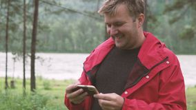 A man watching the news on a mobile phone in a hike stock video footage