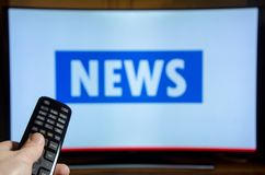 Man watching News on TV and using remote controller stock photo