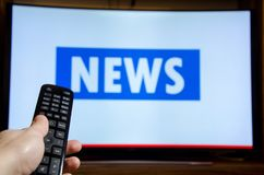 Man watching News on TV and using remote controller.  stock photography