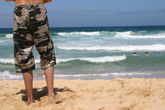 Man watching ocean. Body legs on beach watching his two friends swimming Royalty Free Stock Photography