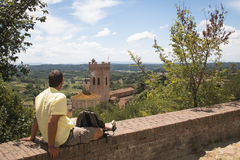 Man watching over Tuscan landscape in San Miniato, Italy. Man relaxing with a view over the impressive landscape in Tuscany near San Miniato in Italy Royalty Free Stock Images