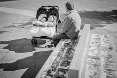 Man watching over two babies in a buggy in Algeciras, Spain. Man sitting on a bench in a public square, watching over two babies asleep in a buggy on a sunny stock photography