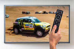 Man is watching paris dakar racing on TV. And holding tv remote controller in hand Stock Images