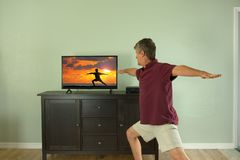 Man watching and participating in yoga class video on tv or internet at home Stock Photos