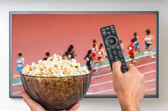 Man is watching running sports game on TV Stock Image