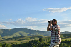 Man Watching Scenic Landscape through Binoculars Royalty Free Stock Photography