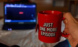 Man Watching series while holding with a cup of tea with netfix. Inspired inscription. Just one more episode. Millennial concept stock photo