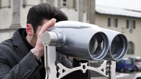Man watching sights through binoculars. Back view of unrecognizable stylish man watching sights through binoculars in winter in Turin, Italy stock footage