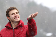 Man watching the snow falling on his hand in winter Stock Images