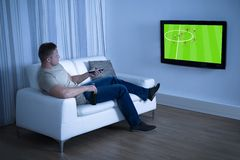 Man watching soccer game on television at home. Man Sitting On Couch Watching Soccer Game On Television At Home Stock Images
