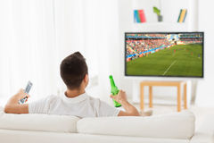 Man watching soccer game on tv and drinking beer. Leisure, technology, mass media and people concept - man watching football or soccer game on tv and drinking Royalty Free Stock Photos
