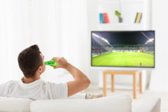 Man watching soccer game on tv and drinking beer Royalty Free Stock Image