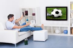 Man watching soccer. Portrait Of An Excited Mature Man Watching Soccer Game On Television Stock Photos