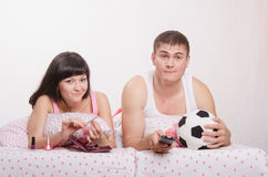 Man watching soccer on TV, manicure girl engaged in bed. Young girl and a guy in bed. Beautiful girl has a manicure, men watches football on TV Royalty Free Stock Photos