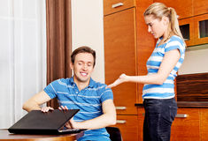 Man watching something on laptop, his wife is angry Stock Images