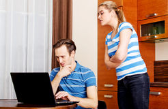 Man watching something on laptop, his wife trying to look what he doing.  Stock Image