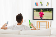Man watching sport on tv and drinking beer at home Royalty Free Stock Images