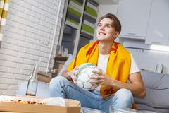Man watching sport on tv at home alone holding ball. Guy watching sport on tv alone wearing scarf of his favorite team holding soccer ball best fan looking at Royalty Free Stock Photo