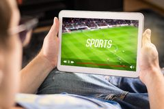 Man watching sports on tablet. Football and soccer game. Man watching sports on tablet. Football and soccer game live stream and video player on screen. Pay per royalty free stock images