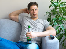 Man watching sports on TV. Man with bottle of beer watching sports on TV Stock Images