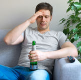Man watching sports on TV. Man with bottle of beer watching sports on TV Royalty Free Stock Images