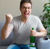 Man watching sports on TV. Man with bottle of beer watching sports on TV Stock Photos