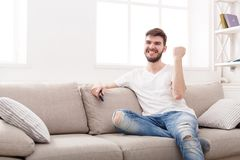 Man watching sports on tv and supporting team. Smiling man watching sports on tv and supporting favorite team, sitting on couch at home, copy space Stock Photos