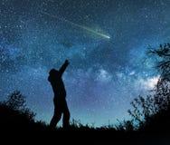 Man watching the stars in night sky. A man watching the stars in night sky royalty free stock photo