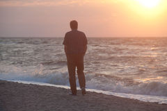 Man watching the sunrise on beach Stock Photo