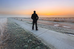 Man watching the sunrise on a cold winter day Stock Photos
