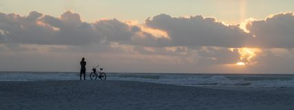 Man watching sunset at the beach with bicycle royalty free stock photography