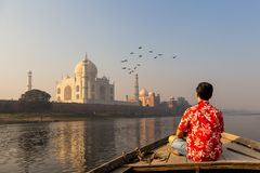 Man watching sunset over Taj Mahal from a wooden boat with bird flying over. Man watching sunset over Taj Mahal from a wooden boat with bird flying over stock image