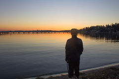 A silhouette of a man watching a winter sunset on a lake at Juanita Bay Park, Kirkland, Washington Stock Images