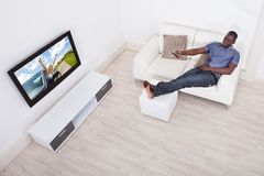 Man watching television Stock Images