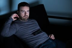 Man watching television on the couch Stock Photo