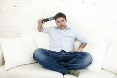 Man watching television at home living room sofa with remote control looking very interested Royalty Free Stock Photos