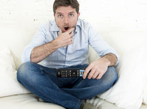 Man watching television at home living room sofa with remote control looking very interested Stock Images