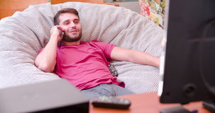 Man Watching Television At Home Then Answering Mobile Phone stock video footage