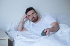 Man watching television lying in bed Stock Image