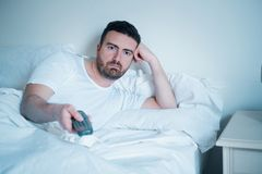 Man watching television lying in bed Royalty Free Stock Image