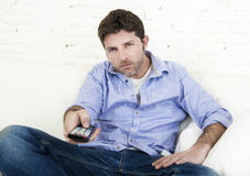 Man watching television lying at home living room sofa with remote control looking very interested Stock Photo
