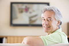 Man watching television smiling Royalty Free Stock Photo