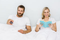 Man watching television while woman reading book. Man watching television while women reading book at bedroom Royalty Free Stock Image