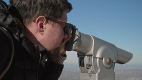 Man is watching in touristic telescope in mountains stock video