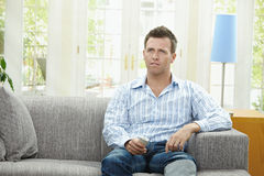 Man watching TV. At home, sitting on couch, holding remote control in hand Stock Photos