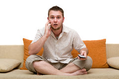 Man watching tv. Casual man watching tv on sofa Royalty Free Stock Images