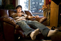 Man watching tv. A man watching tv holding remote control towards tv Stock Photo