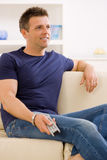 Man watching TV. At home, sitting on beige couch, holding remote control in hand Royalty Free Stock Photography