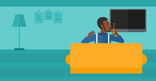 Man watching TV. An african-american man sitting on the couch in living room and watching tv with remote controller in one hand and a bottle in another vector Stock Photography