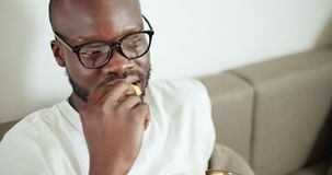 Man Watching TV. Afro-american man dressed in white shirt eating snacks while watching TV, home leisure concept stock video footage